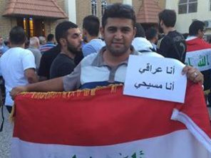 "A Muslim standing outside a church in Baghdad holding a sign that reads: ""I am Iraqi, I am Christian"""