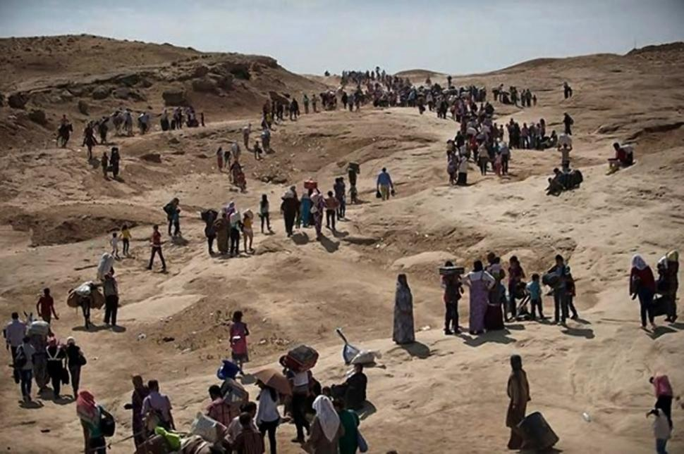 Displaced Iraqis from the northern town of Sinjar flee to the mountains, seeking refuge after Islamic State extremists seized their hometown and vowed to execute them. Photo from New York Daily News